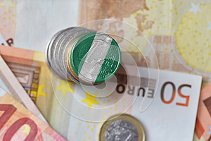 Euro coin with national flag of nigeria on the euro money banknotes background.