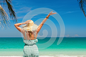 joyful woman with arm up on beach in summer during holidays travel.