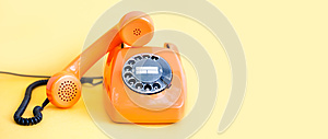 Vintage phone busy handset receiver on yellow background. Retro style orange telephone communication call center concept