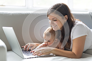 Mother and baby child are looking to play and read computer on the couch at home