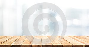 Wood table top on blur glass window wall building background