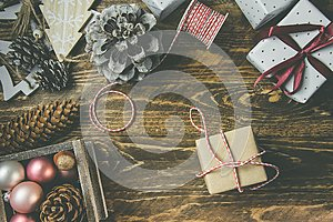 Flat lay on rustic aged wood background, Christmas or New Years gits wrapped in craft brown white paper. Ribbon,twine,pine cones
