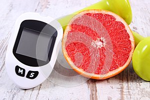 Glucometer for measuring sugar level, fresh grapefruit and dumbbells for fitness, healthy lifestyles concept