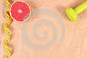 Fresh grapefruit, tape measure and dumbbells for fitness, healthy lifestyles concept