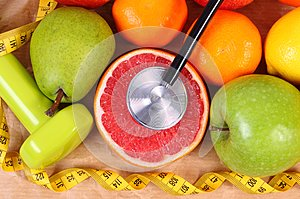 Fresh ripe fruits, tape measure, stethoscope and dumbbells for fitness, healthy lifestyles concept
