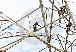 Electricians working on pylon construction tower