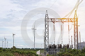 high voltage electrical power pylon substation  with wind turbines renewable wind energy