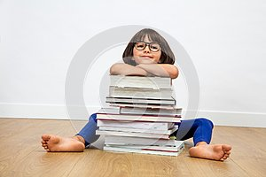 Smiling primary child with eyeglasses leaning on pile of books