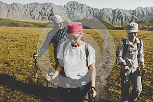 Group Of Hikers Walking Along The Plain In Summer Mountains, Journey Travel Trek Concept