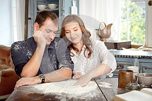 Young couple in the kitchen playing with flour. Funny moments, smiles, cooking, Happy together, memories.