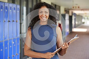 Middle aged black female teacher smiling in school corridor