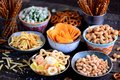 Different Kinds Of Snacks - Chips, Salted Peanuts, Cashews, Peas With Wasabi, Pretzels With Salt, Potatoes, Salted Straw. Royalty Free Stock Image - 101717956