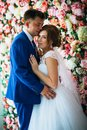 Beautiful Bride And Groom On The Background Of A Wall Of Flowers Stock Photos - 101919353
