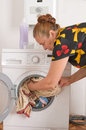 The Woman Loads Linen Into A Washing Machine. Stock Image - 10210391