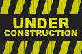 Under Construction Warning Sign With Yellow And Black Stripes Painted Over Cracked Wood. Royalty Free Stock Image - 102137216