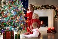 Children At Christmas Tree. Kids At Fireplace On Xmas Eve Stock Photography - 102400792