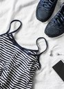 Women`s Sports Clothing On A Light Background. Sports Women`s Tank Top With Thin Spaghetti Straps, Striped, Running Sneakers, Ph Royalty Free Stock Photos - 103074538