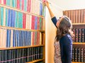 Girl Reaching For A Book On Bookshelf Royalty Free Stock Image - 103568366