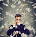 Busy Businessman Looking At Wrist Watch, Talking On Mobile Phone Under Cash Rain. Time Is Money Concept Royalty Free Stock Photography - 104532357