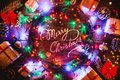 Wooden Background With Colored Lights And Stars. Surrounded By Gifts And Cones. With Merry Christmas Center Message. Royalty Free Stock Images - 105123799