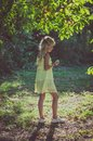 Little Lovely Girl In Yellow Dress Standing Under The Tree Royalty Free Stock Photo - 105729945