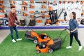 A Guy And A Girl Are Posing On The Camera With A Lawn Mower. Royalty Free Stock Photo - 105796315