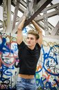 Handsome Blond Young Man Hanging From Concrete Structure Stock Photos - 105905383