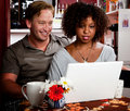 Mixed Race Couple In Coffee House With Laptop Comp Royalty Free Stock Image - 10696436