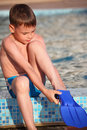 Boy Puts On Flipperson Border Of Pool Royalty Free Stock Images - 10698999