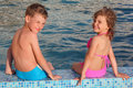 Boy And Girl Sit On Border Of Pool Stock Image - 10699001