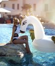 Woman Relaxing In Luxury Swimming Pool Resort Hotel On Big Inflatable Unicorn Floating Pegasus Float Stock Images - 108126334