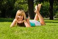 Young Smiling Girl Lies On Grass Royalty Free Stock Image - 10830576
