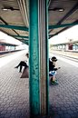 Young Boy And Girl Sitting And Waiting A Train While Using Their Cellphones Royalty Free Stock Photo - 108618035