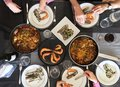 Top View Of Family Eating Spanish Tapas Around A White Table From High View Angle Stock Photo - 112118000
