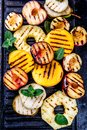 GRILLED FRUITS. Grill Fruits - Pineapple, Peaches, Plums, Avocado, Pear On Black Cast Iron Grill Board Royalty Free Stock Photography - 112407627
