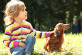 Little Girl With Dachshund Sits On Grass Stock Photos - 11411253