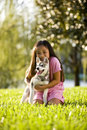 Young Asian Girl Hugging Puppy Sitting On Grass Stock Images - 11550334