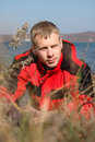 Young Blond Man In Red Jacket Sit On The Seashore. Stock Photography - 11677552