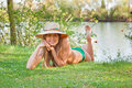 Young Blond Girl With A Hat Lying On The Grass Stock Photography - 12192072