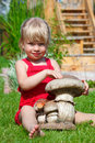 The Girl On A Lawn Sits With A Toy Mushroom Royalty Free Stock Photo - 12263145