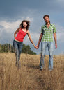 Happy Couple Walking On A Field Stock Image - 12400511