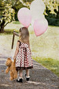Child Carrying Balloons And Dragging Her Teddy Royalty Free Stock Photography - 12485957
