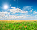Green Field Under Blue Cloudy Sky Whit Sun Royalty Free Stock Photography - 13291417