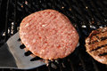 Flipping Hamburgers On The Grill Stock Photography - 13399372
