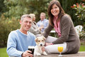 Couple With Pet Dog Outdoors Enjoying Drink In Pub Stock Image - 13674101