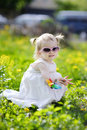 Adorable Girl Sitting In Dandelion Field Stock Images - 14349724