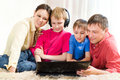 Family Lying On The Carpet With A Laptop Royalty Free Stock Photos - 14512528