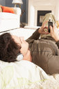 Man Listening To MP3 Player Laying On Rug Stock Photos - 14724933