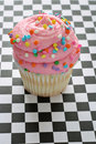 Pink Sprinkle Cupcake On Checkered Background Royalty Free Stock Images - 14882209