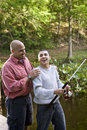 Hispanic Teenager And Father Fishing In Pond Stock Photos - 15051383